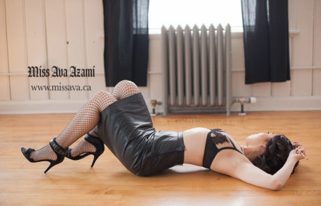 Miss Ava Azami Posing on the Ground. Wearing Leather Skirt, Heels, and Bralette.